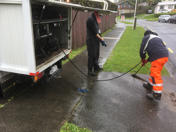 et flush truck releases water at high pressure to dislodge or clean out drains